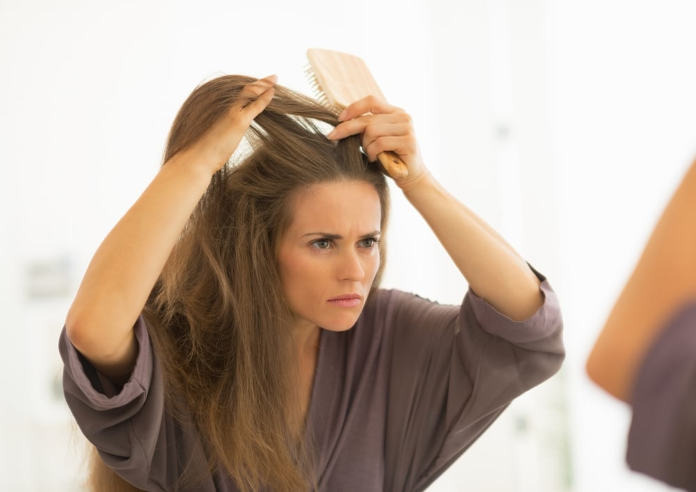 woman combing and damaging hair