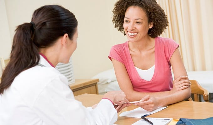 woman talking to doctor about estrogen dominance and migraines